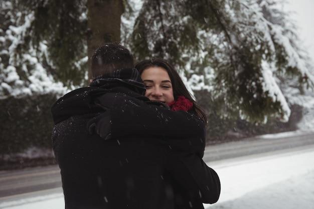 Romantisch paar omarmen in bos tijdens de winter