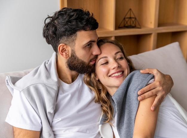 Romantisch paar op de bank die thuis elkaar houdt