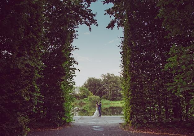 Romantisch paar pasgetrouwden, bruid en bruidegom staat en bedrijf boeket bloemen en groen, groen in de tuin. huwelijksceremonie op de natuur.