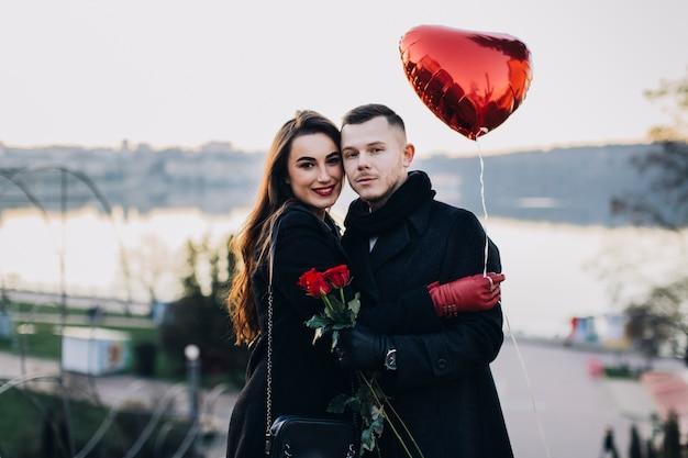 Romantisch paar poseren op camera met ballon
