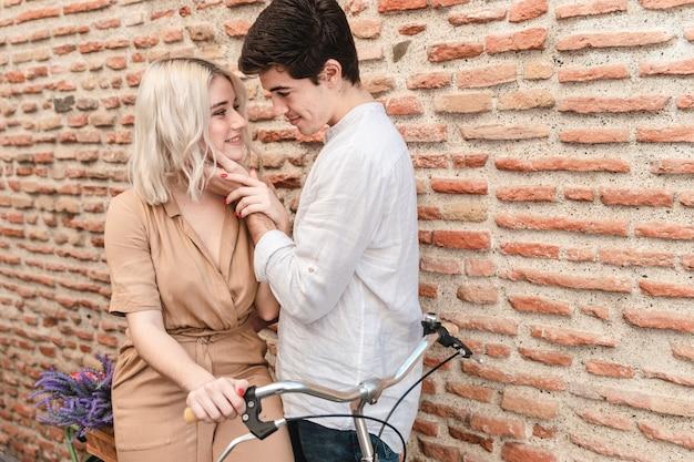 Romantisch paar poseren tegen bakstenen muur met fiets