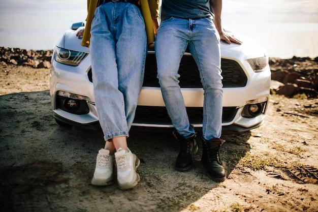 Romantisch paar staat in de buurt van een muscle car op het strand. de knappe bebaarde man en een aantrekkelijke jonge vrouw hebben een liefdesverhaal.