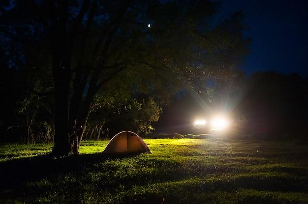 Romantisch paar toeristen hebben een rust bij een kampvuur in de buurt van verlichte tent