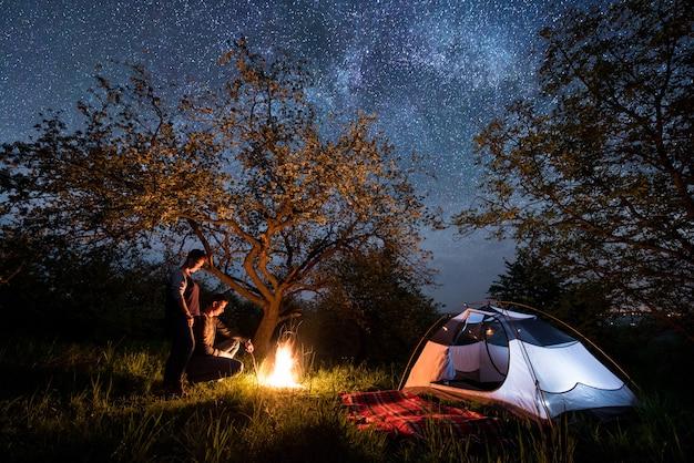 Romantisch paar toeristen staan bij een kampvuur in de buurt van tent onder bomen en prachtige nachtelijke hemel vol sterren en melkweg. nacht kamperen