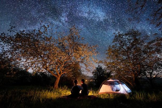 Romantisch paar toeristen zitten bij een kampvuur in de buurt van tent onder bomen en prachtige nachtelijke hemel vol sterren en melkweg.