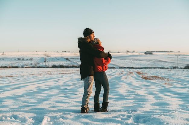 Romantisch paar verliefd dragen van warme kleren knuffelen en kussen zachtjes in besneeuwde winterlandschap