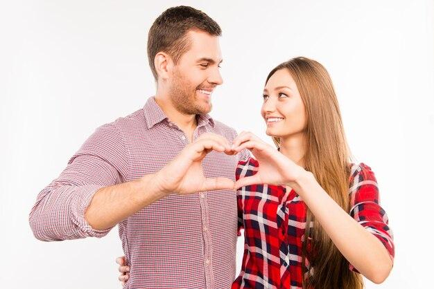 Romantisch paar verliefd gebaren een hart met vingers