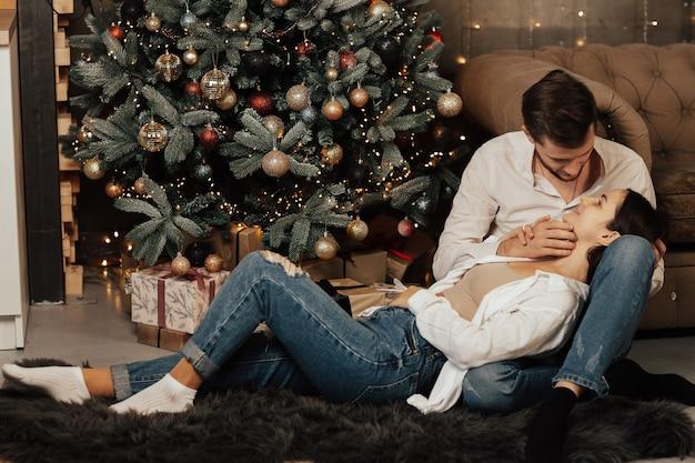 Romantisch paar verliefd in de buurt van de kerstboom thuis.