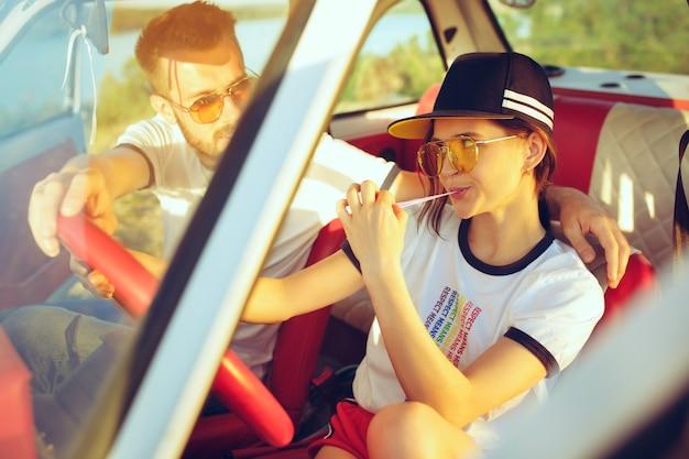 Romantisch paar zittend in de auto tijdens een road trip lachen op zomerdag