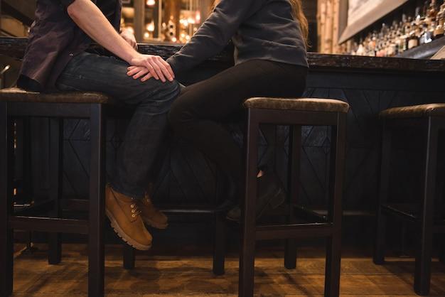 Romantisch paar zittend op kruk bij toog