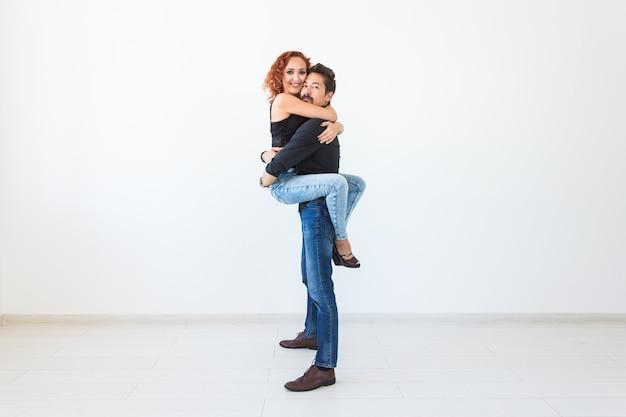 Romantisch, passie, mensen concept - jong koppel dansen met passie op witte muur met kopie ruimte