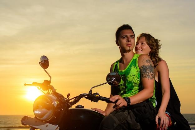 Romantisch plaatje met een paar mooie stijlvolle motorrijders bij zonsondergang. knappe man met tatoeage en jonge sexy vrouw vermaken zich in motor trip