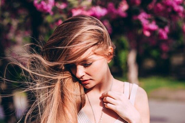 Romantisch portret van charmante blonde op de muur van een bloeiende tuin. boom met roze bloemen. blonde vrouw van de schoonheid met lang haar in openlucht. kersebloesem. portret close-up. sakura