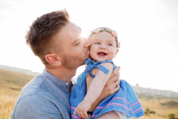 Romantisch portret van een gelukkige vader die zijn lachend dochtertje in openlucht houdt. papa kust zijn lieve kleine peuter van het babymeisje. gelukkige fathers day-conceptenfoto - zie dicht omhoog onder ogen