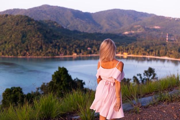 Romantisch portret van jonge kaukasische vrouw in zomerjurk genieten van ontspannen in het park op de berg met prachtig uitzicht op de tropische zee.vrouw op vakantie reizen rond thailand gelukkige vrouw bij zonsondergang