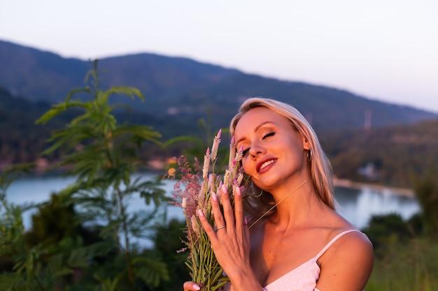 Romantisch portret van jonge kaukasische vrouw in zomerjurk genieten van ontspannen in park op berg met prachtig uitzicht op de tropische zee