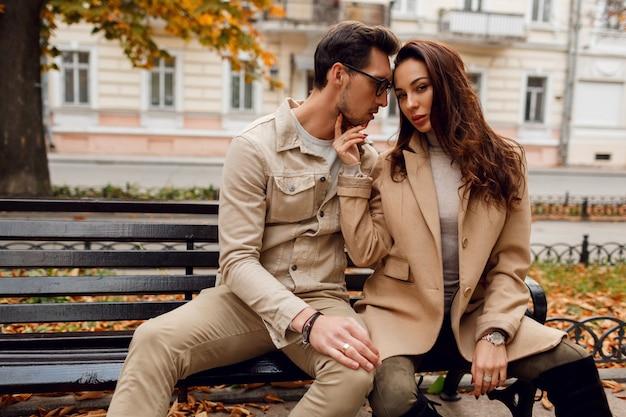 Romantisch portret van jonge mooie paar verliefd knuffelen en zoenen op bankje in herfst park. stijlvolle beige jas dragen.