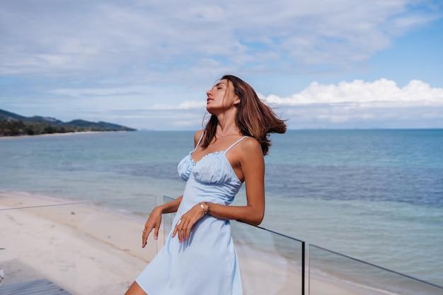Romantisch portret van vrouw in blauwe lichte jurk alleen op tropisch strand, zonnige dag, gebruinde donkere huid