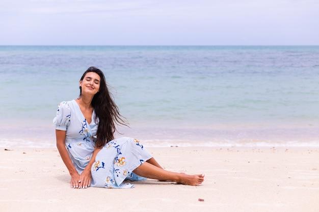Romantisch portret van vrouw in lange blauwe jurk op strand door zee op winderige dag