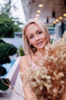 Romantisch portret van vrouw in roze leuke avondkleding houdt wilde bloemen buiten tropische luxevilla mooie vrouw met boeket