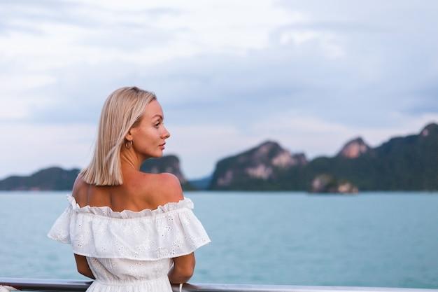 Romantisch portret van vrouw in witte kleding die op grote bootveerboot varen
