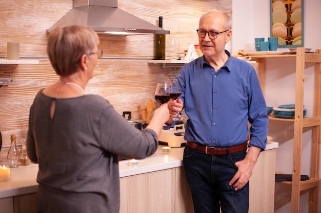 Romantisch senior koppel dat herinneringen deelt en roostert met glazen rode wijn. ouder paar verliefd praten met een aangenaam gesprek tijdens een gezonde maaltijd.