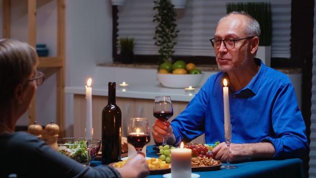 Romantisch senior koppel dat het huwelijk thuis viert, in de keuken aan tafel zit, rode wijn drinkt en gezond voedsel eet. mooie vrouw en knappe man genieten van tijd samen doorbrengen.