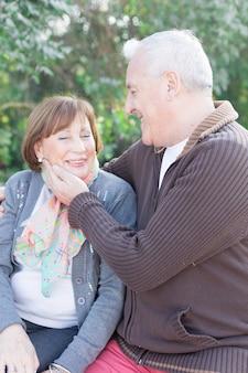 Romantisch senior man te raken de wang van zijn vrouw