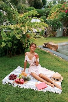 Romantisch sierlijke aziatische model zittend op deken, wijn drinken en genieten van zomerpicknick in tropische tuin.