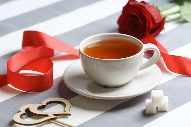Romantisch stilleven met een kopje thee en fel rode vakantieattributen.