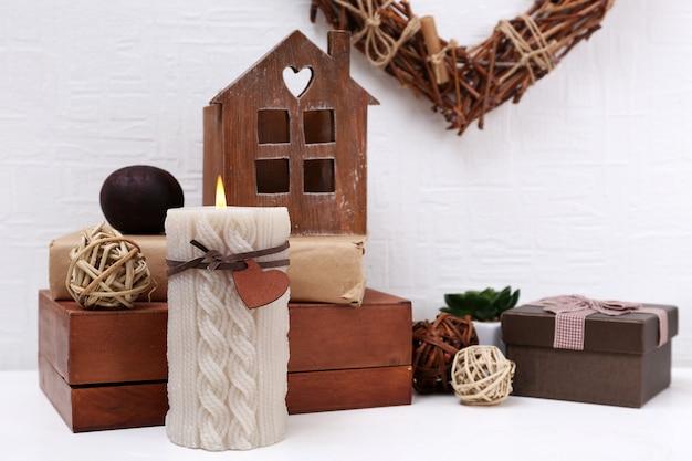Romantisch stilleven met rieten hart en designdetails op plank en witte muur