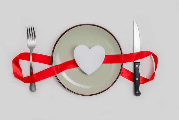 Romantisch valentijnsdag diner idee concept. hart op plaat en zilveren slijtage op witte achtergrond.
