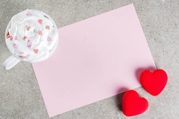Romantisch, valentijnsdag. stenen tafel met blanco papier voor brief, gefeliciteerd, warme chocolademelk met slagroom en zoete harten, versierd met papier rode harten, bovenaanzicht