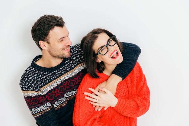 Romantisch verliefde paar omhelzen elkaar en hebben plezier samen, dragen warme gebreide truien, staan tegen wit