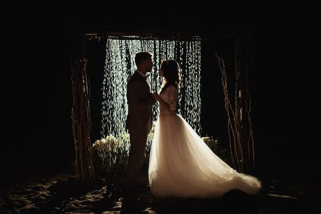 Romantisch verliefde paar pasgetrouwden, bruiloft tegen de achtergrond van de nachtelijke hemel en regen. de bruid en bruidegom staan op de achtergrond van de boog met regen.