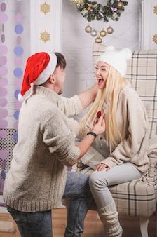Romantisch verlovingsvoorstel (huwelijk) op kerstavond, gelukkige jonge mensen in liefde - liefde en verlovingsconcept