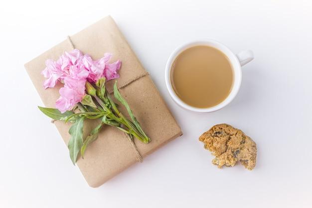 Romantisch vintage stilleven met mooie geschenkdoos omwikkeld met bruin kraftpapier en versierd met roze bloem op witte achtergrond
