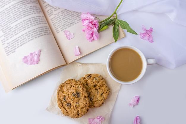 Romantisch vintage stilleven met roze bloemen, oud boek, kopje thee of koffie met melk en haverkoekjes