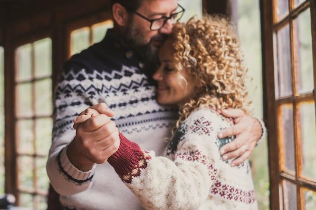 Romantisch volwassen paar dat thuis danst met liefde en relatie. man en vrouw dansen samen met emotie en gevoel. gelukkig flirtend paar geniet van vrije tijd in de winter