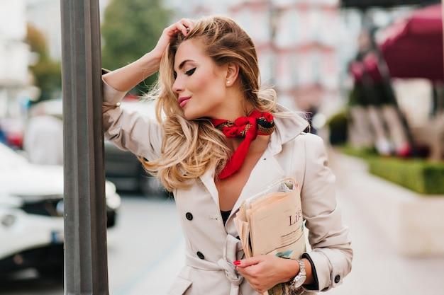 Romantisch vrouwelijk model in lichtbruin jasje poseren met gesloten ogen niet ver van park