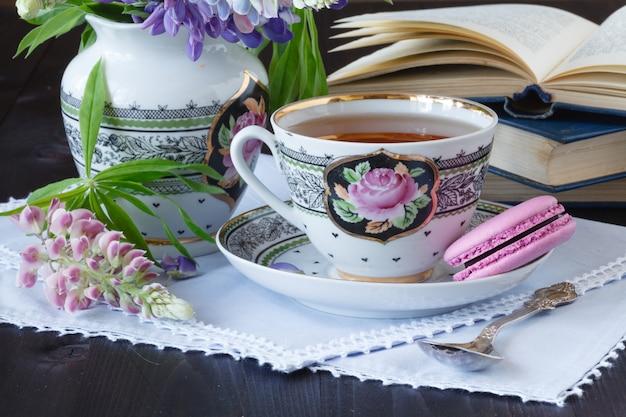 Romantische achtergrond met kopje thee bloemen en open boek over witte tafel