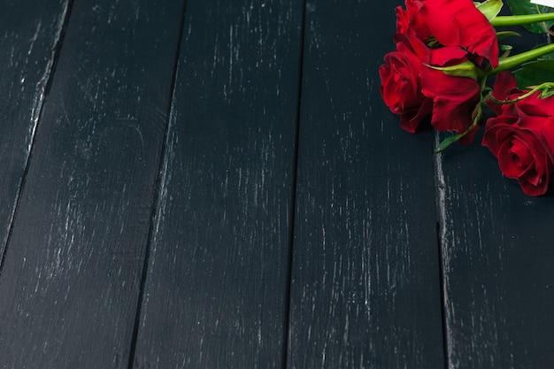 Romantische achtergrond met rode roos op houten tafel