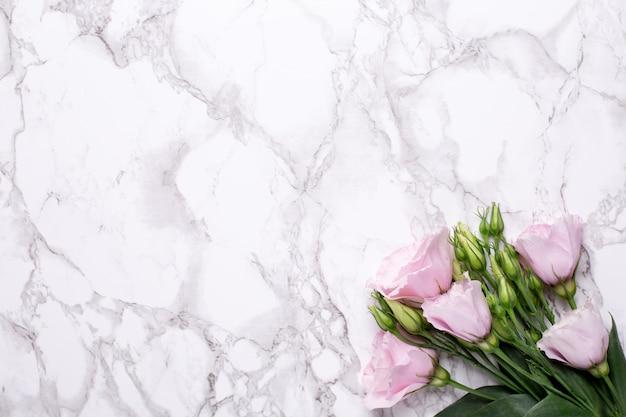 Romantische achtergrond met roze bloemen op marmeren tafel