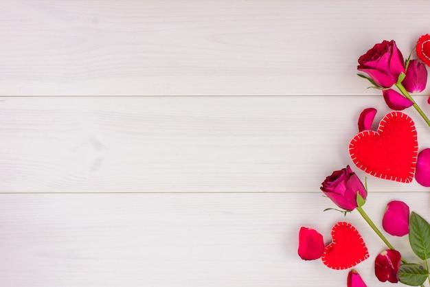 Romantische achtergrond met rozen en harten op een witte houten tafel. bovenaanzicht, kopie ruimte.