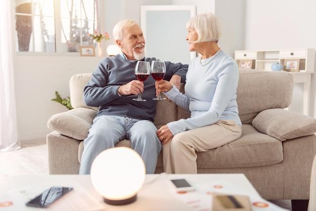 Romantische avond. aangenaam ouder echtpaar zittend op de bank en wijn drinken tijdens de viering van hun huwelijksverjaardag terwijl ze elkaar liefdevol aankijken
