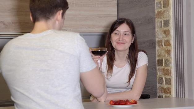 Romantische avond. man en vrouw aan een tafel met wijn en aardbeien.
