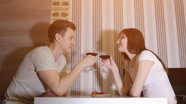 Romantische avond. man en vrouw aan tafel wijn drinken, zonlicht