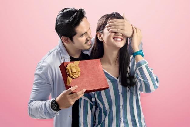 Romantische aziatische mens die zijn meisjeeogen behandelt en hem een verrassing geeft