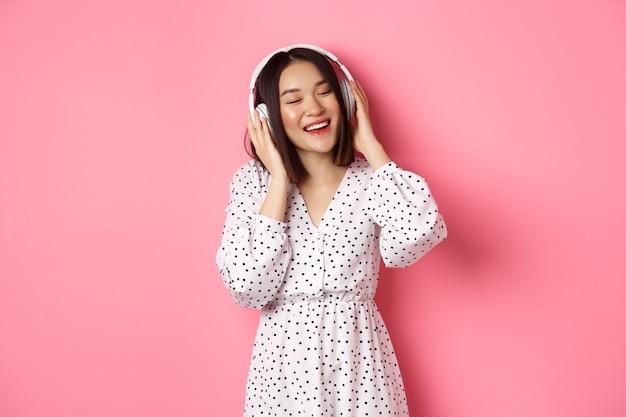 Romantische aziatische vrouw die gelukkig lacht, muziek luistert in een koptelefoon en danst, staande in trendy jurk over roze achtergrond