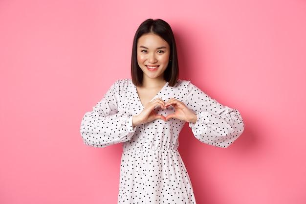 Romantische aziatische vrouw die hartteken toont, ik hou van je gebaar, schattig glimlachend in de camera, staande in jurk over roze achtergrond.